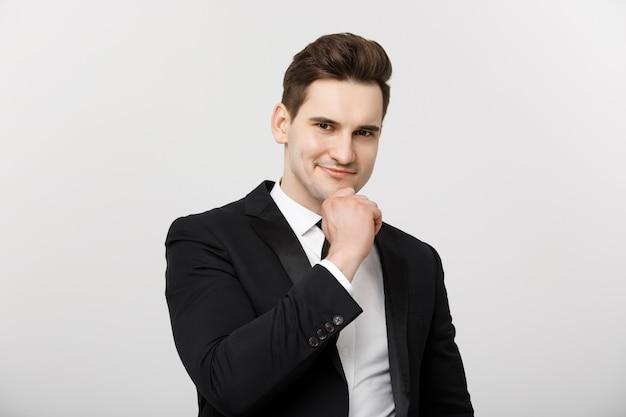 Koncepcja biznesowa uśmiechnięty zamyślony przystojny mężczyzna stojący na białym tle i dotykający ...