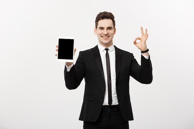 Koncepcja biznesowa: wesoły biznesmen w eleganckim garniturze z tabletem pc wyświetlono ok. na białym tle nad szarym tłem.
