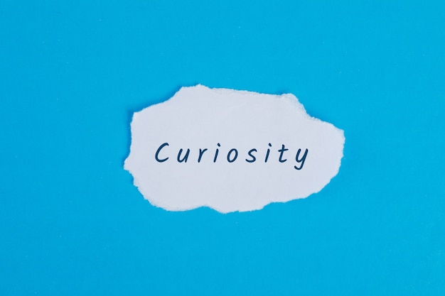 Koncepcja biznesowa ze słowem ciekawość na podartym papierze na niebieskim stole leżał płasko.