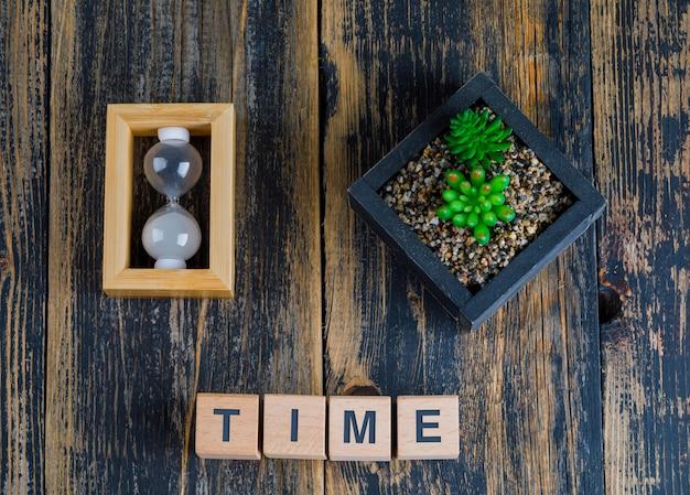 Koncepcja biznesowa ze słowem czasu na drewnianych kostkach, klepsydrze i roślin
