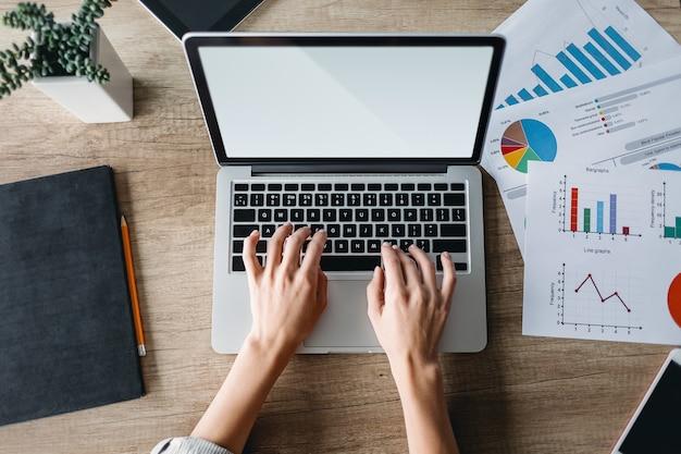 Koncepcja biznesu, edukacji, ludzi i technologii - zbliżenie kobiecych rąk z laptopem, gadżetami, wykresami i rośliną w doniczce