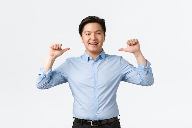 Koncepcja biznesu, finansów i ludzi. dumny i bezczelny azjatycki przedsiębiorca z aparatami na zębach skierowanymi na siebie, popisywanie się lub chwalenie się osiągnięciem, stojący na białym tle.