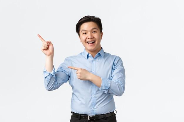 Koncepcja biznesu, finansów i ludzi. entuzjastycznie uśmiechnięty azjatycki przedsiębiorca męski w niebieskiej koszuli, z aparatami na zęby, wskazującymi palcami w lewym górnym rogu, dokonującym ogłoszenia, białe tło