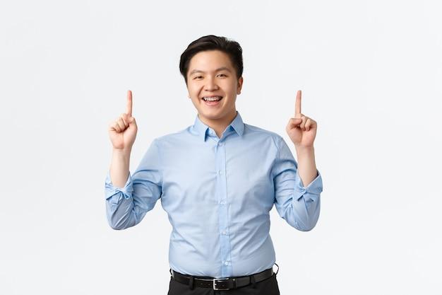 Koncepcja biznesu, finansów i ludzi. optymistyczny, przystojny azjatycki biznesmen w niebieskiej koszuli, wskazujący palce w górę i uśmiechnięty szczęśliwy, pokazujący ogłoszenie, sprzedawca poleca produkt