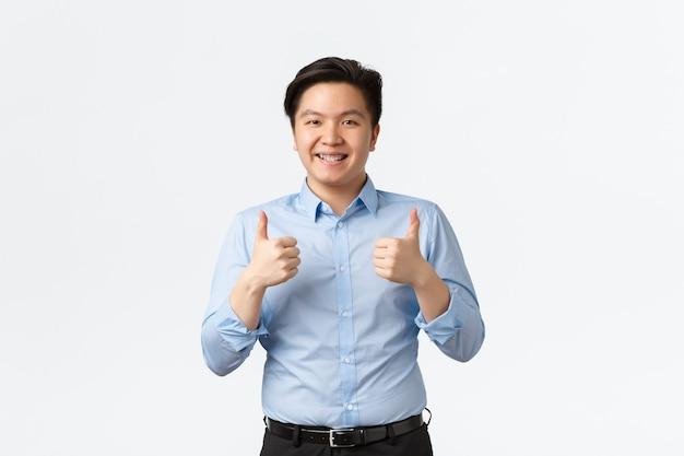 Koncepcja biznesu, finansów i ludzi. optymistyczny przystojny azjatycki mężczyzna przedsiębiorca, japoński sprzedawca z szelkami, pokazujący kciuk w górę z aprobatą, polecający usługę lub firmę
