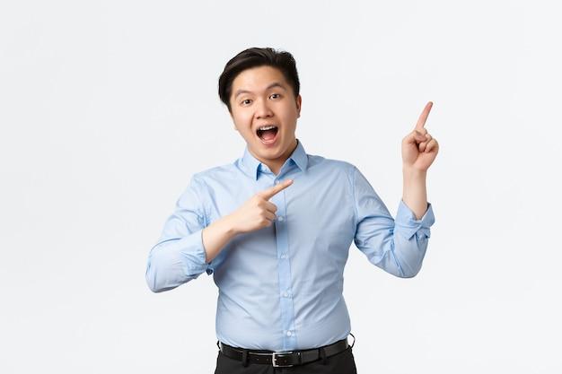 Koncepcja biznesu, finansów i ludzi. podekscytowany szczęśliwy azjatycki biznesmen pokazuje baner produktu, wskazując prawy górny róg z zadowolonym uśmiechem, wygłaszając mowę lub ogłaszając ogłoszenie.