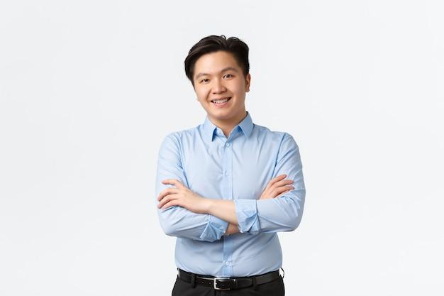 Koncepcja biznesu, finansów i ludzi. profesjonalny pewny siebie azjatycki biznesmen z aparatami ortodontycznymi, uśmiechnięty zadowolony, skrzyżowane ramiona w klatce piersiowej, stojący na białym tle, sprzedawca pokazujący produkt