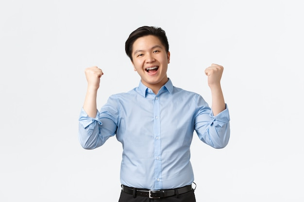 Koncepcja biznesu, finansów i ludzi. zwycięski biznesmen azjatycki z aparatami ortodontycznymi, pompującą pięścią w radości, uśmiechnięty jak triumfujący nad zwycięstwem, osiągający cel, stojący na białym tle.
