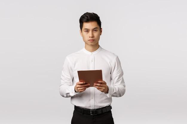 Koncepcja biznesu, finansów i rekrutacji. przystojny elegancki młody azjatykci mężczyzna trzyma cyfrową pastylkę i patrzeje poważny, jest zajęty, kontroluje pracę zdalną, hr przeprowadza wywiad wnioskodawców