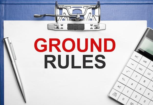 Koncepcja biznesu i finansów. na stole zeszyt, długopis, kalkulator i teczka z napisem ground regules