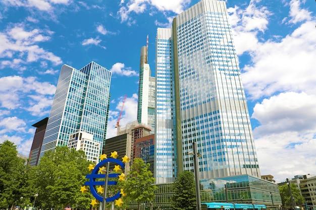Koncepcja biznesu i finansów z gigantycznym znakiem euro w siedzibie europejskiego banku centralnego w godzinach porannych, dzielnica biznesowa we frankfurcie nad menem, niemcy