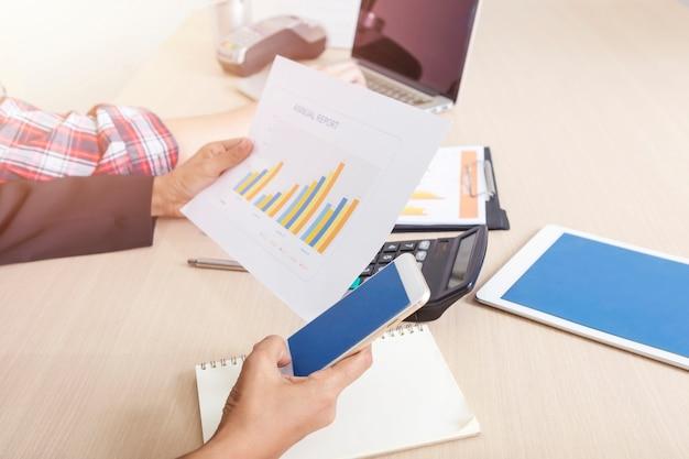 Koncepcja biznesu i finansów. zbliżenie ludzi pracujących w biurze z raportem mobilnym i papierkowej roboty.