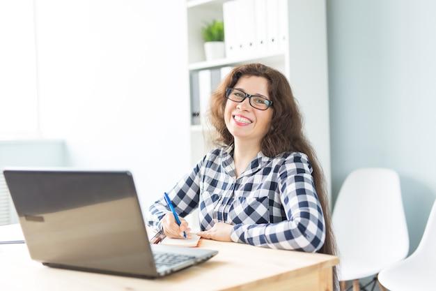 Koncepcja biznesu i ludzi - młoda uśmiechnięta kobieta siedzi w biurze i pracy