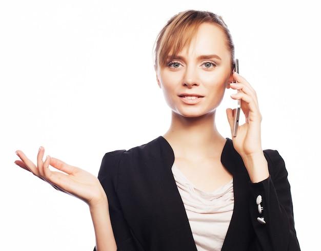 Koncepcja biznesu, ludzi i biura: młoda kobieta biznesu z telefonu komórkowego. pozytywne emocje. na białym tle.