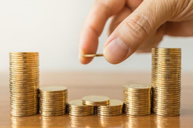 Koncepcja biznesu, pieniędzy, finansów, bezpieczeństwa i oszczędności. zamyka up mężczyzna ręki mienie i stawia monetę brogować monety na drewnianym stole.
