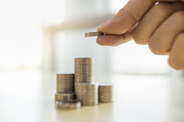 Koncepcja biznesu, pieniędzy, finansów, bezpieczeństwa i oszczędności. zamyka up mężczyzna ręki mienie i stawia trzy monety brogować złociste monety na drewnianym stole.