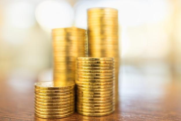 Koncepcja biznesu, pieniędzy, finansów, bezpieczeństwa i oszczędności. zamyka up sterta złociste monety na drewnianym stole pod światłem słonecznym z kopii przestrzenią.