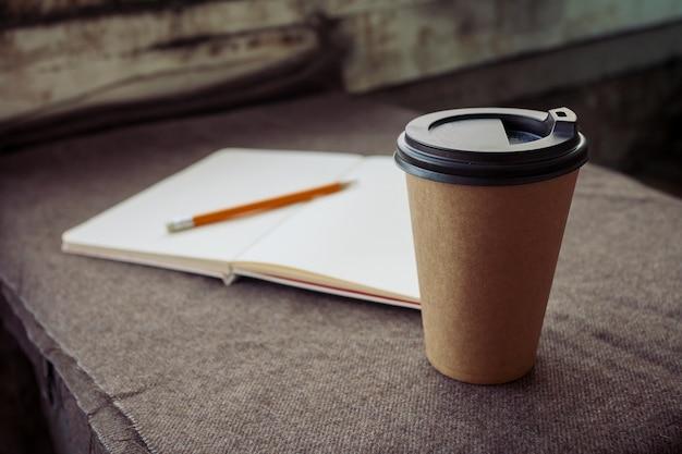Koncepcja biznesu, stylu życia, jedzenia i kawy - ołówek, notatnik i papierowa filiżanka kawy na brązowym tle tkaniny