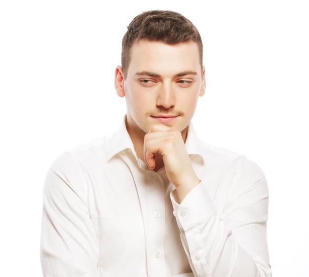 Koncepcja biznesu, sukces i ludzie - młody człowiek biznesu myślenia, na białym tle.