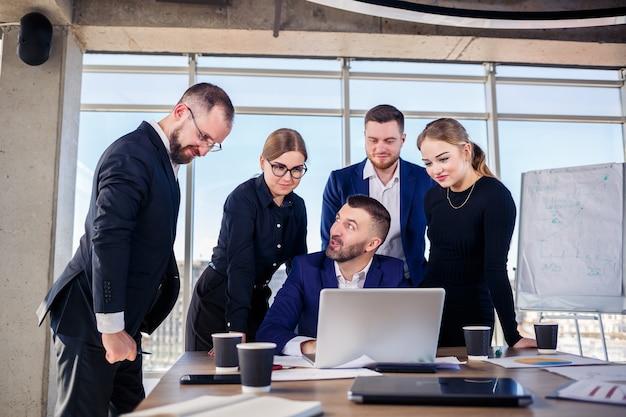Koncepcja biznesu, technologii i biura - szczęśliwy zespół biznesowy z laptopami, dokumentami i kawą. spotkanie przed rozpoczęciem dnia roboczego w celu omówienia biznesplanu
