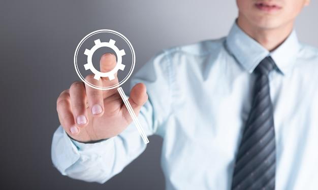 Koncepcja biznesu, technologii i internetu. biznesmen naciska przycisk z ikoną mechanizmu