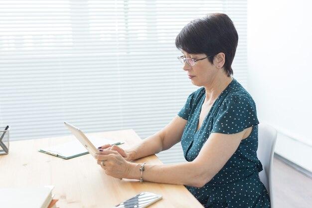 Koncepcja biznesu, technologii i ludzi - poważna kobieta siedzi w biurze i korzysta z tabletu