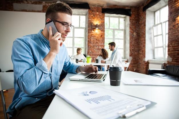 Koncepcja biznesu, uruchamiania i ludzi - szczęśliwy biznesmen lub kreatywny mężczyzna pracownik biurowy z komputera dzwoniąc na smartfonie.