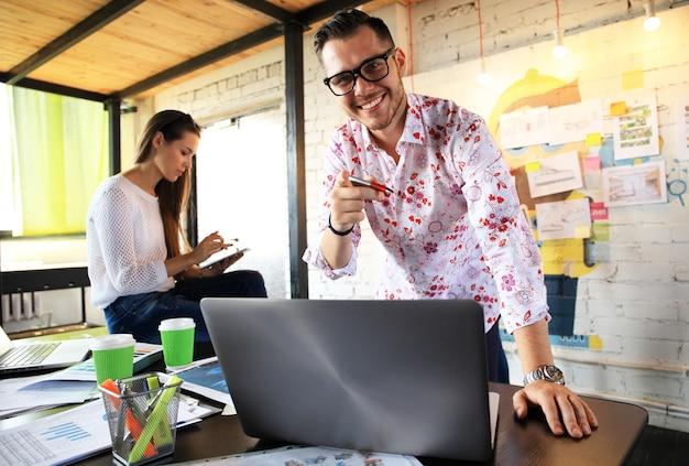 Koncepcja biznesu, uruchamiania i ludzi - szczęśliwy biznesmen lub twórczy mężczyzna pracownik biurowy z komputerem