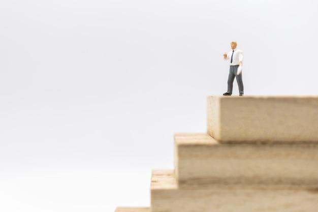 Koncepcja biznesu, zarządzania i planowania. biznesmen miniaturowa postać stoi i pracuje na górze stosu drewniana bloack zabawka