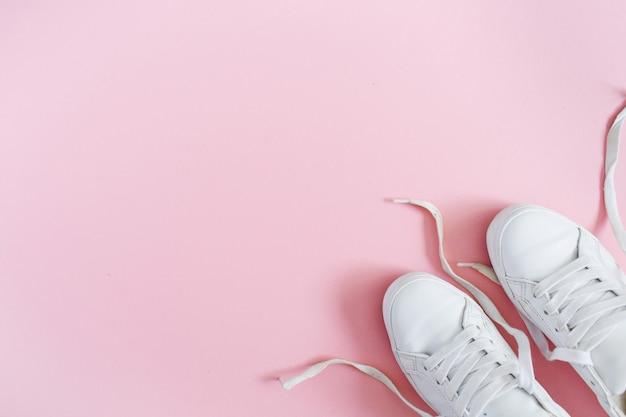 Koncepcja bloga mody. białe trampki damskie na różowym tle