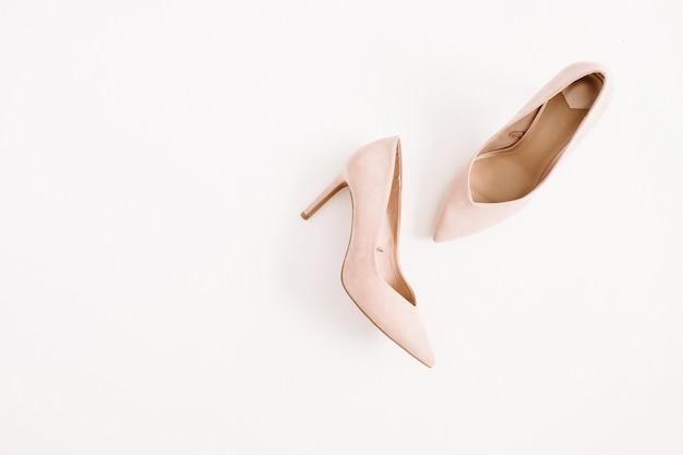 Koncepcja bloga mody. jasnoróżowe damskie buty na wysokim obcasie na białym tle. płaski układanie, widok z góry