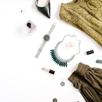 Koncepcja bloga piękności. kobiece ubrania i akcesoria: zielona spódnica i sweter, zegarki, naszyjnik, szminka, buty, okulary przeciwsłoneczne na białym tle. płaski świeckich, widok z góry modne tło kobiece moda.
