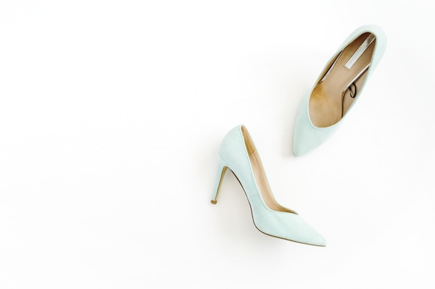 Koncepcja bloga uroda. bladoniebieskie buty damskie na białym tle.