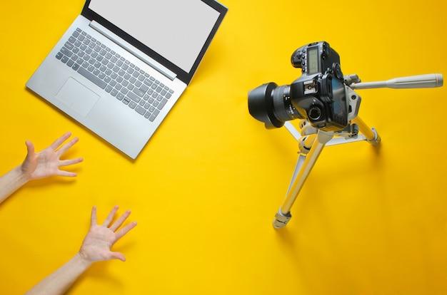 Koncepcja blogera online. recenzent emotikonów. kobiece ręce pokazują emocjonalnie blog z aparatem na statywie, laptopie. minimalizm.