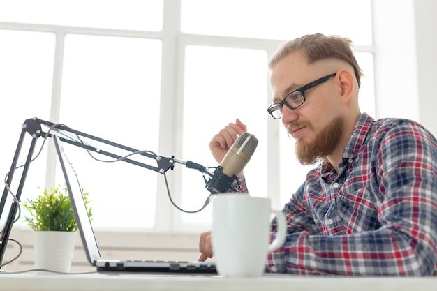 Koncepcja blogera, streamera i ludzi - zabawny młody człowiek dj pracujący w radiu