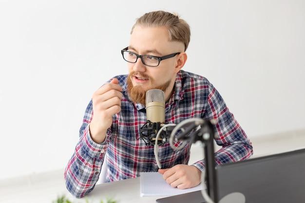 Koncepcja blogera, streamera i ludzi - zbliżenie śmiesznego młodego mężczyzny dj pracującego w radiu