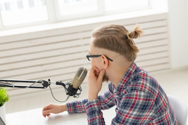 Koncepcja blogera, streamera i nadawania - młody człowiek dj pracujący w radiu.