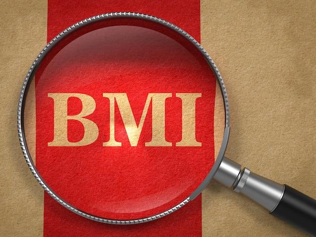 Koncepcja bmi. lupa na starym papierze z tłem czerwona linia pionowa.