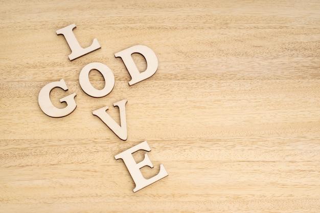 Koncepcja bóg jest miłością. słowa tworzące krzyż na drewnianym stole.
