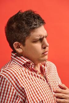 Koncepcja bólu. piękny portret męski na czerwonym tle