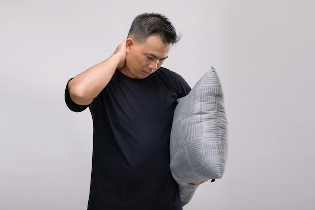 Koncepcja bólu szyi: portret azjatyckiego mężczyzny trzymającego szarą poduszkę i czującego się zmęczony lub bóle szyi.