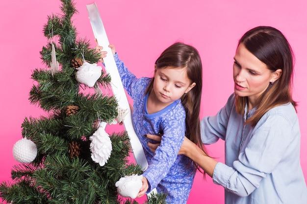 Koncepcja boże narodzenie, dzieciństwo i ludzie - dziecko dziewczynka stojąca na drabinie dekorującej drzewo
