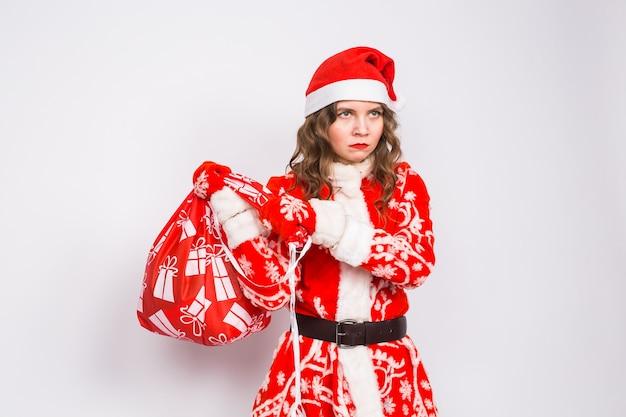 Koncepcja boże narodzenie, emocje i ludzie - zły kobieta w ubraniach świętego mikołaja, trzymając prezenty na białej ścianie.