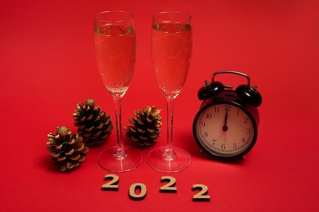 Koncepcja boże narodzenie i nowy rok. flety szampana z winem musującym, budzik pokazujący północ na tarczy zegara, złote szyszki i drewniane cyfry 2022, na czerwonym tle z miejscem na kopię