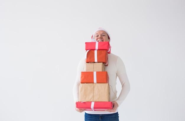 Koncepcja boże narodzenie i święta - mężczyzna w santa hat z wieloma prezentami na białym tle z miejscem na kopię with