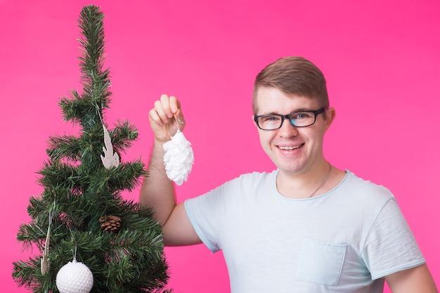 Koncepcja boże narodzenie i wakacje - portret uśmiechnięty mężczyzna z choinką na różowej ścianie.