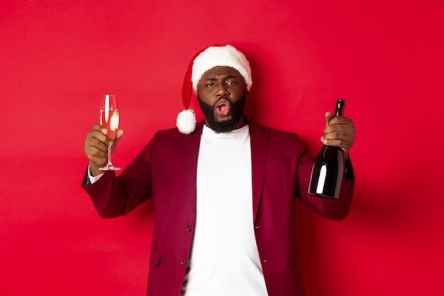 Koncepcja boże narodzenie, imprezy i święta. wesoły mężczyzna cieszy się nowy rok, w kapeluszu santa, podnosząc kieliszek i butelkę szampana, bawiąc się na czerwonym tle.