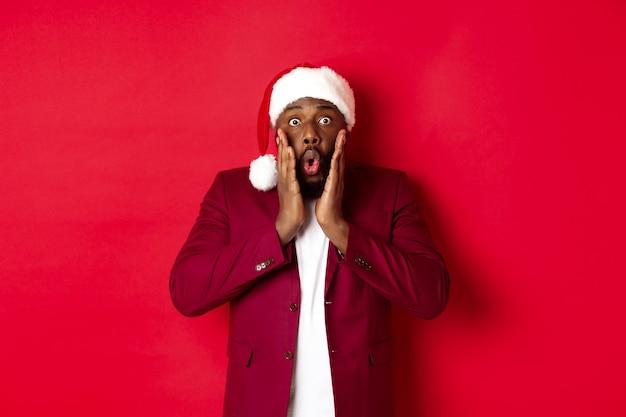 Koncepcja boże narodzenie, imprezy i święta. zszokowany murzyn w santa hat reagujący na ofertę noworoczną, stojący na czerwonym tle.