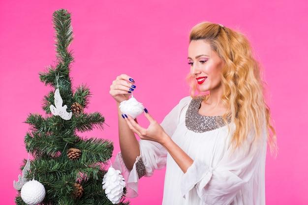 Koncepcja boże narodzenie, święta i ludzie - młoda szczęśliwa blondynka dekorująca choinkę na różowej przestrzeni.
