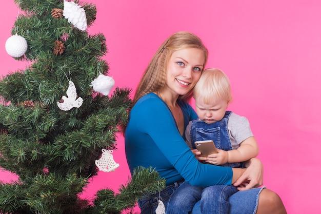 Koncepcja boże narodzenie, święta, technologie i ludzie - młoda szczęśliwa kobieta przytula córkę w pobliżu choinki. dziecko korzystające z telefonu komórkowego.